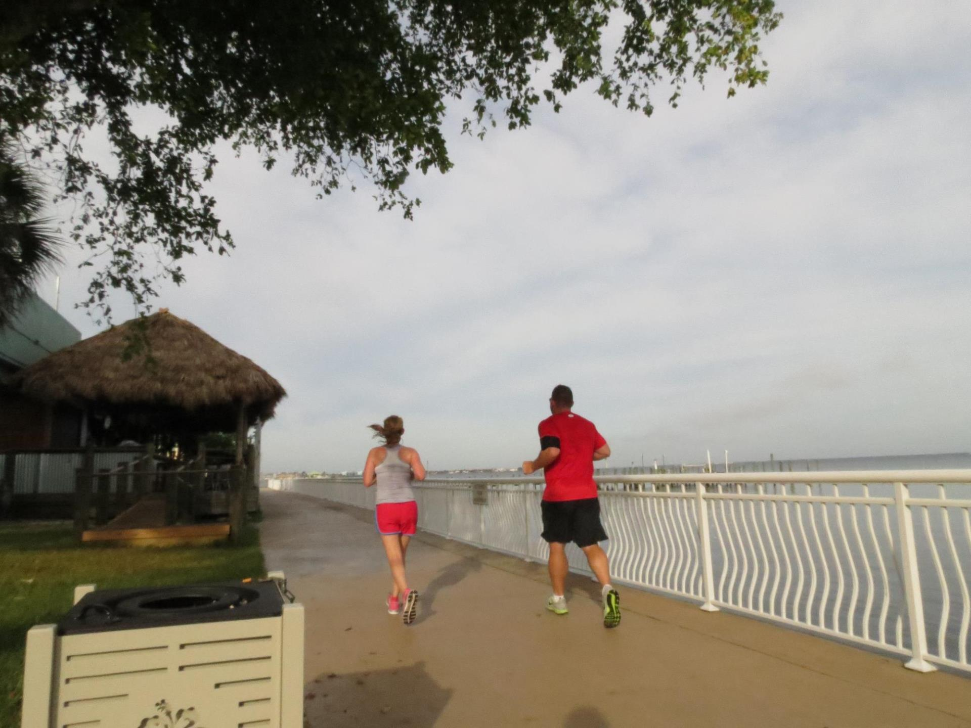 two people running along the harbor