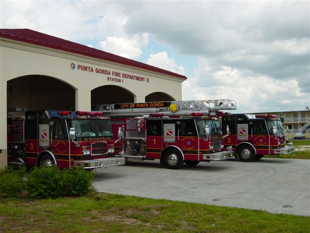 Photo of exterior - Fire Station 1 located at 1410 Tamiami Trail. Three fire trucks parked outside of garage doors.