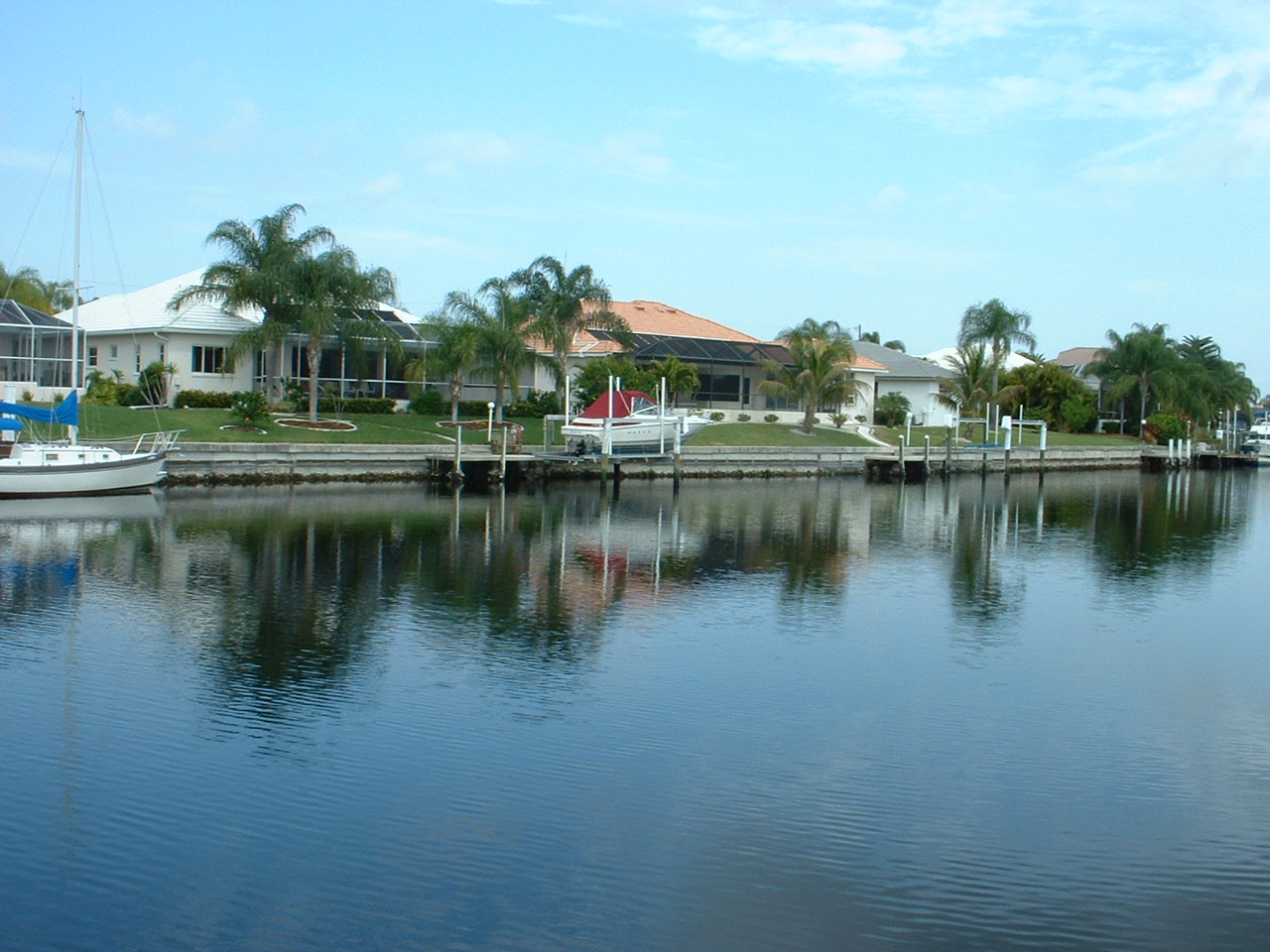 Image of canal with homes, and docked boats.