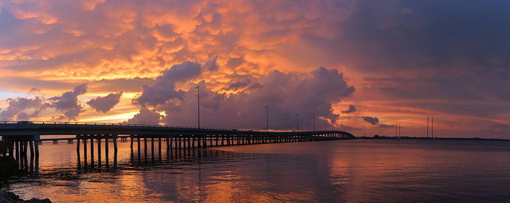 Photo of bridge with evening sunset and clouds.