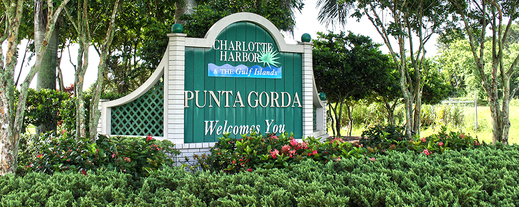Photo of Punta Gorda Welcome Sign sent in landscaped area of trees and shrubs.