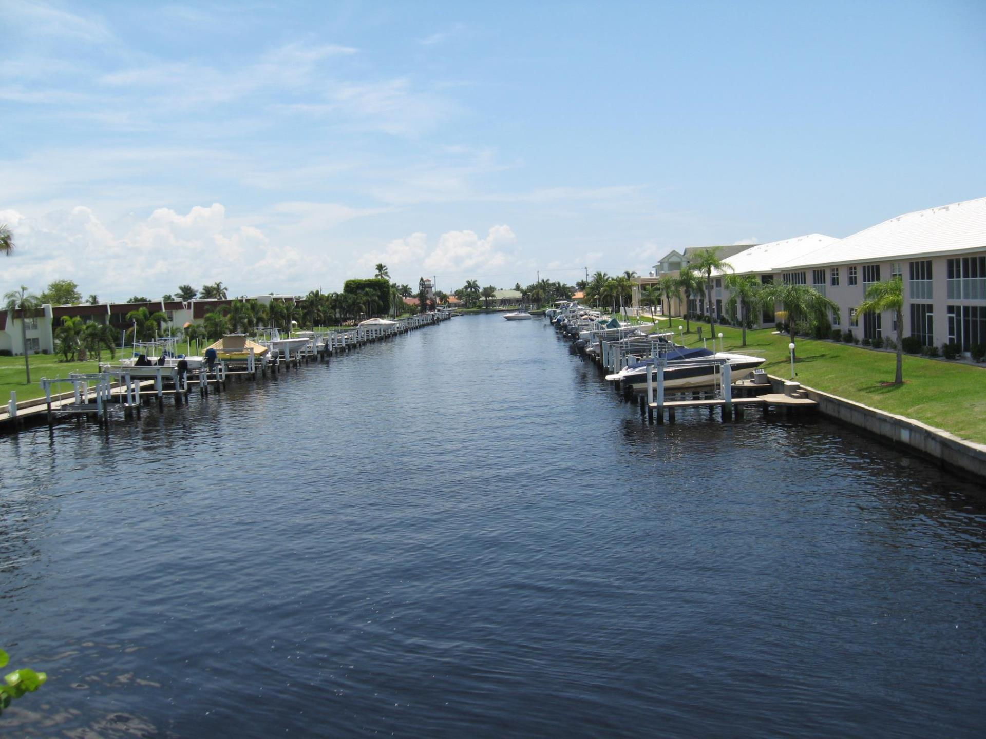 Image of canal with boats docked. Homes in background.