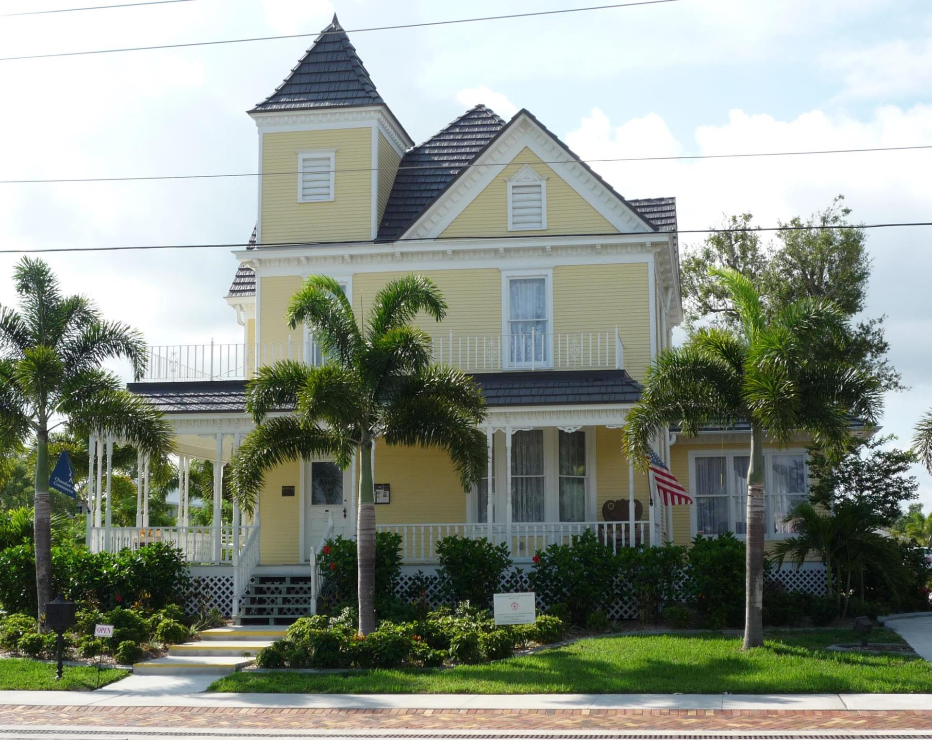 Photo of AC Freeman House. Historical two story yellow home white trim with wrap around porch